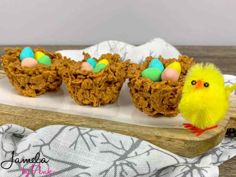 side view of edible birds nest easter dessert recipe with a yellow baby chick next to a wood cutting board holding the nests