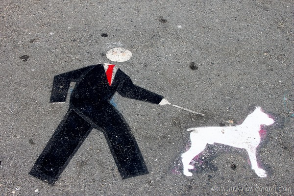 Man in suit walking dog leash sign