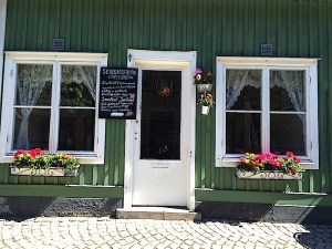 The front of a cafe painted green with white door and windowsills and flower boxes on a sunny Midsummer Day morning in Vaxholm, Sweden. By C.S. White