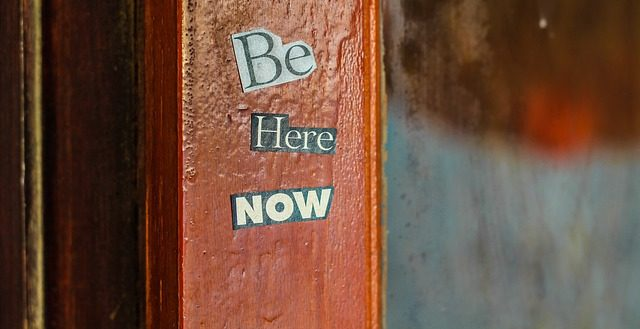 a poster saying be here now