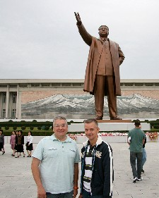 Jim Augusto and Jon Cramer in front of statue of Kim Il Sung inPyongyang