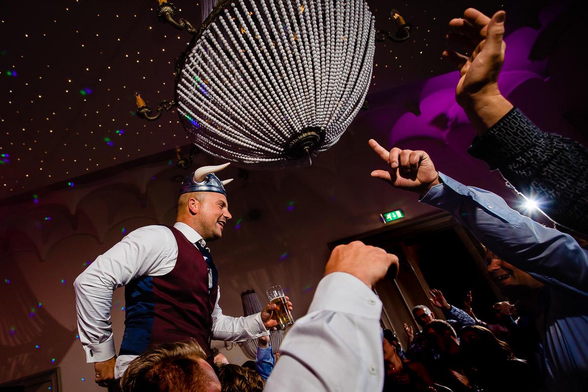 bruidegom wordt opgetild tijdens het feest door zijn vrienden