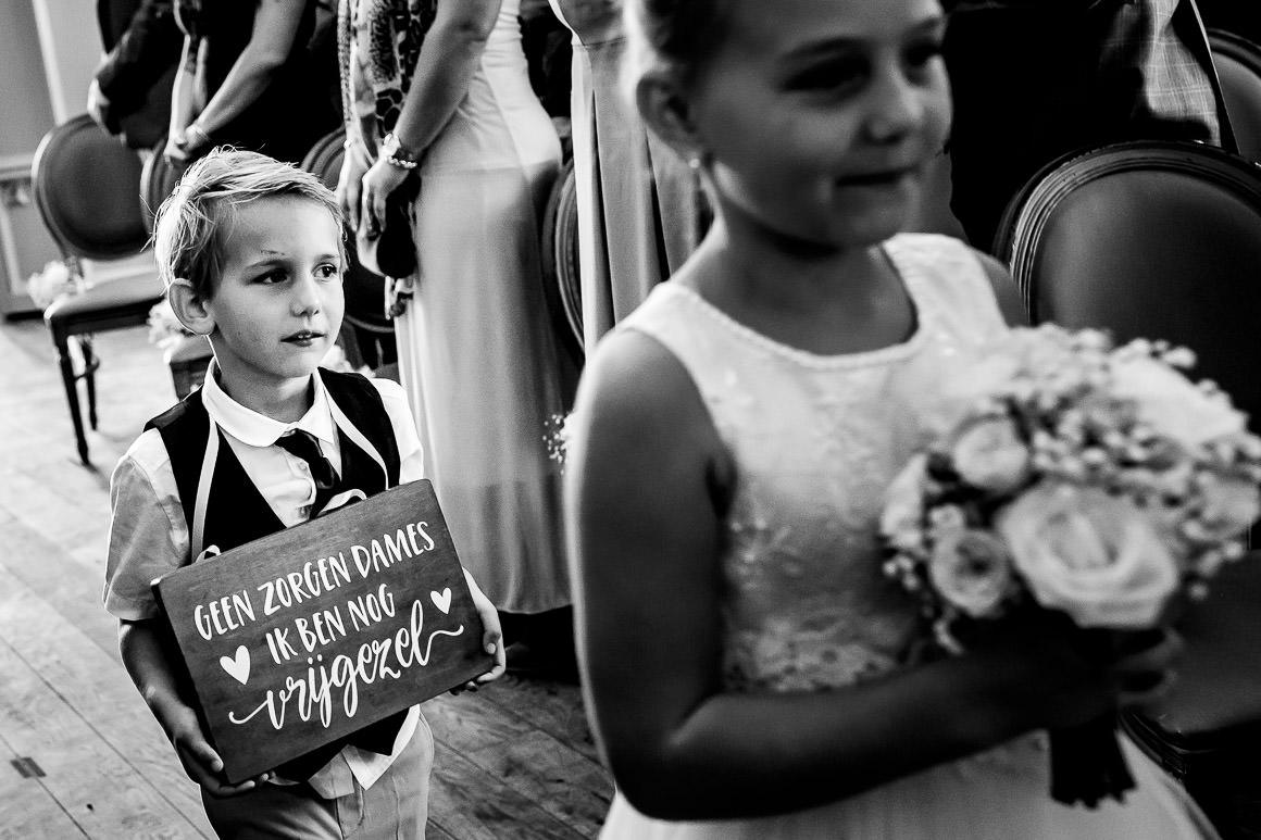 neefje van bruidspaar komt binnen met bordje geen zorgen ik ben nog vrijgezel