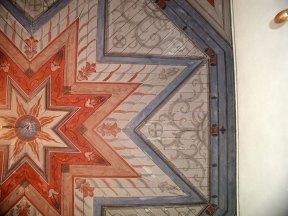 Detalj av takmålning. De ljusa partierna, eller fläckarna, visar färgbortfall.