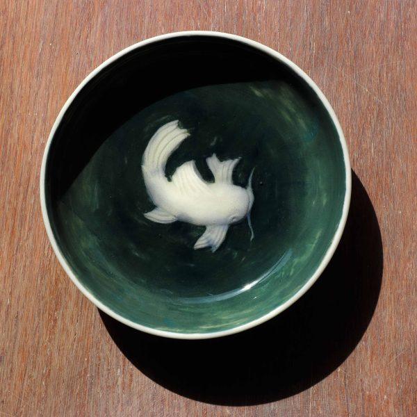 coupelle en porcelaine gravée nageant dans un émail vert transparent