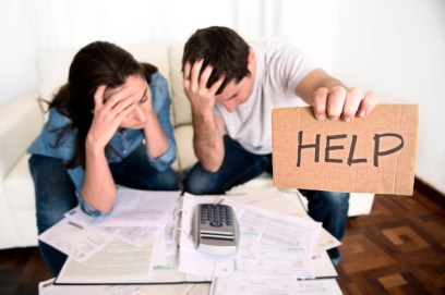 Couple stressed out and holding up a help sign