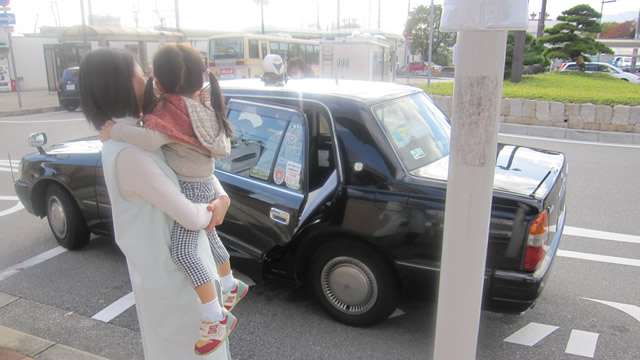 受診のためにタクシーに乗るスタッフとお子さま