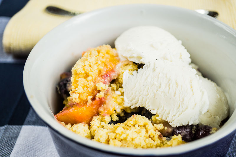bowl of peach blueberry cobbler with ice cream