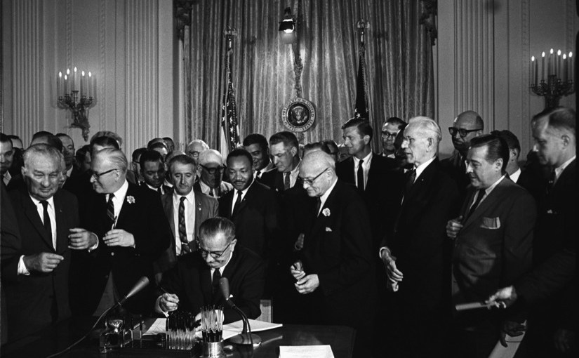 President Lyndon B. Johnson signs the 1964 Civil Rights Act as Martin Luther King, Jr., and others, look on. (Public Domain)