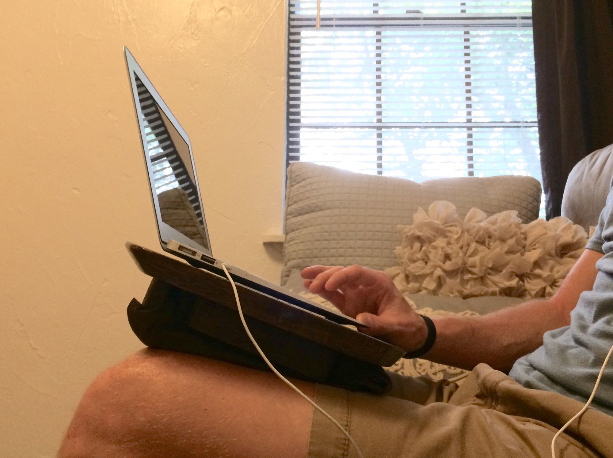 And image of Nick using the lap desk on a couch.