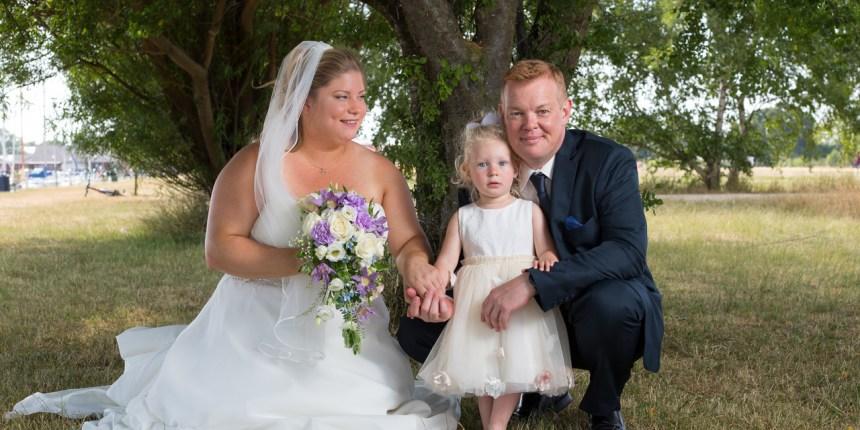 brudepar med datter på græsplæne