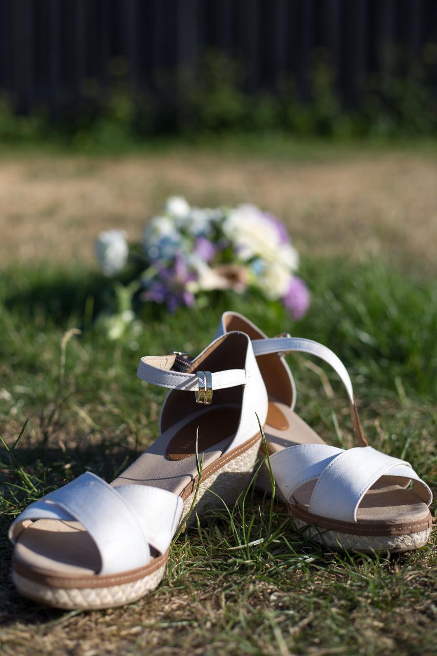 Sko og vielsesringe, med buket i baggrunden