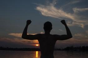 silhouette af mand ved solnedgang over vandet