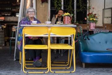 Kvinne sidder bag et gul bord, med to gule plastik stole og nogle gule blomster.