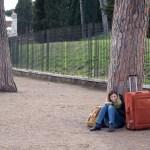 en kvinne med sin orange kuffert og gule taske, siddende op af et træ på grusstien