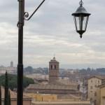 Fin gammel lygtepæl danner rammen om en udsigt ud over byens tage