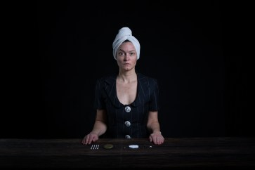 Sitting in a suit, with a towel on the head, behind a desk with skin picking tools laid out