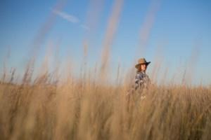 model med cowboyhat, blå himmel og højt græs