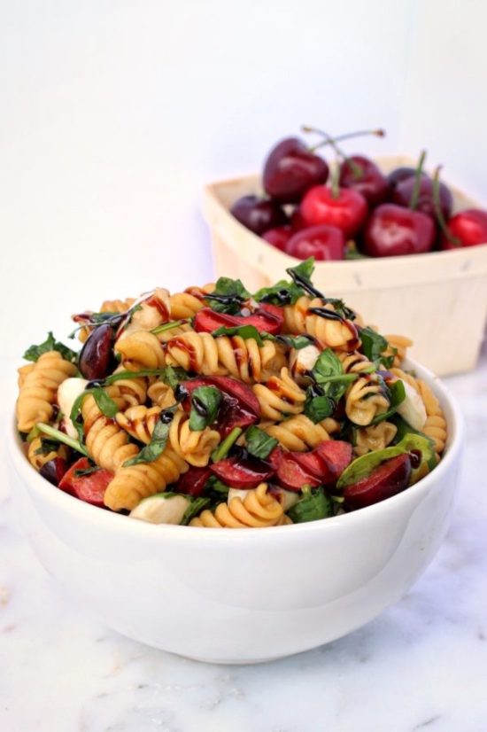 Cherry Caprese Pasta Salad is the perfect addition to your next summer BBQ! Sweet, juicy cherries, fresh mozzarella, and basil come together for a quick, easy meal or side dish! | www.bytesizednutrition.com