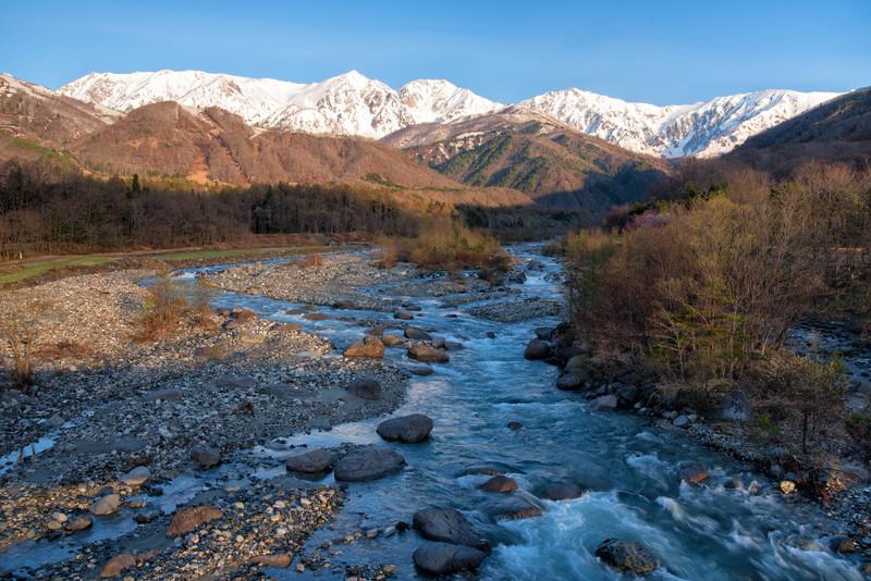 雪山と林の中を流れる川