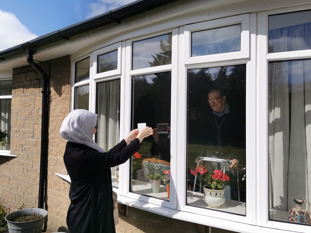 Woman shows a scan image to a man through a window