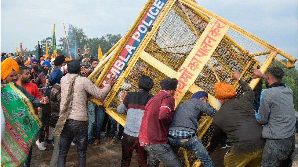 Farmers remove a police barricade in Haryana in protest