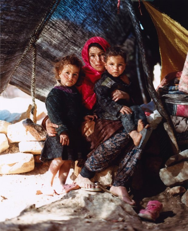 A mother and two children pose for a portrait in a shelter