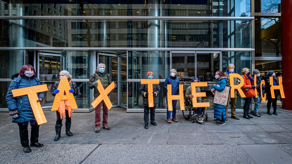 Protesters hold signs saying tax the rich