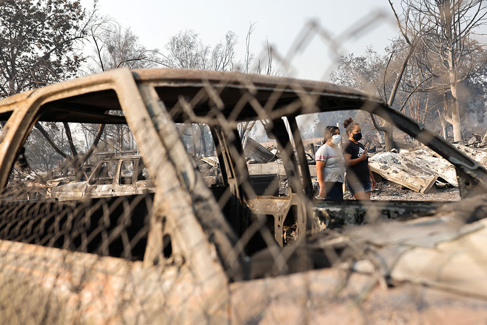 People walk behind off a burned car after wildfires destroyed an area of Phoenix, Oregon