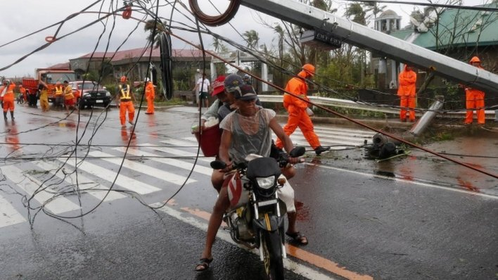 Filipino villagers move past a toppled electric post in the typhoon-hit town of Tigaon, Camarines Sur, Philippines, 01 November 2020