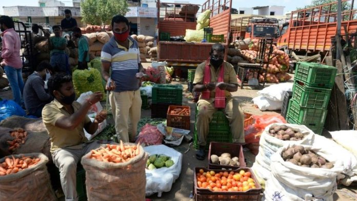 A farmer (C) negotiates prices with traders at a wholesale vegetable market in Hyderabad on August 31, 2020.
