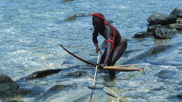 A Jarawa man standing in water with a bow and arrow