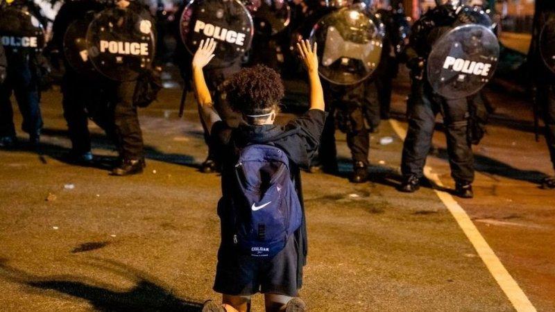 Una manifestante se arrodilla y levanta las manos delante de una fila de policías frente a la Casa Blanca.
