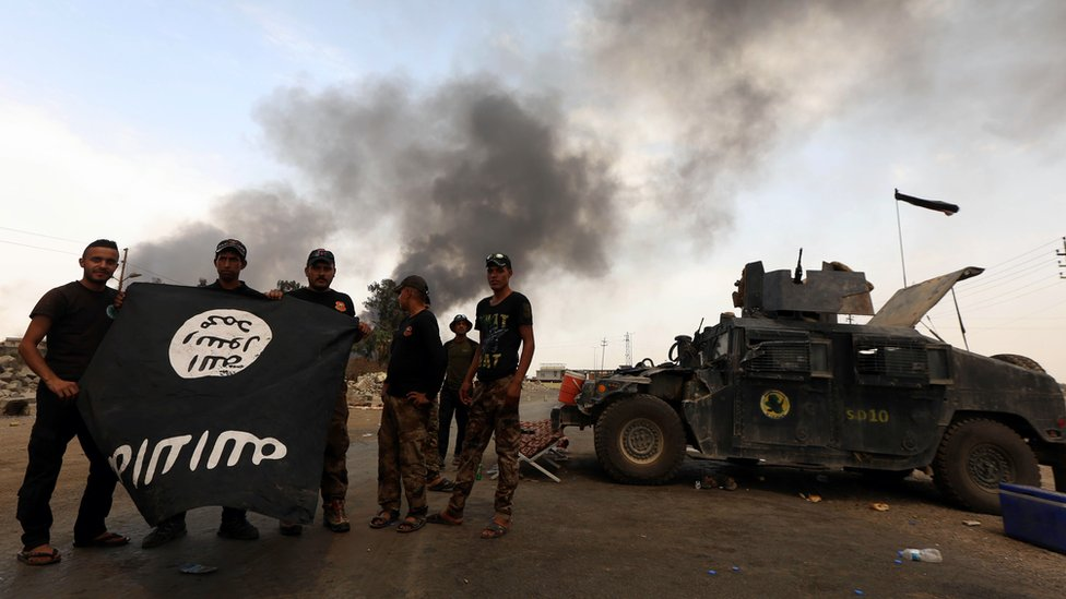 Agentes de seguridad iraquíes muestran una bandera de EI, tras recuperar una zona bajo control de los islamistas.