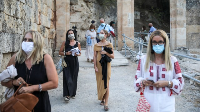 People wearing protective face masks enter the ancient amphitheatre of Epidaurus