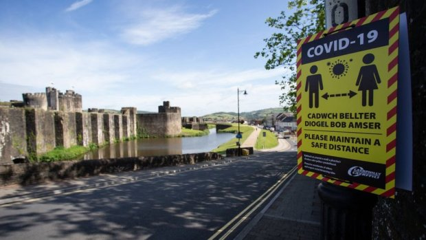 A Covid-19 poster in the foreground with Caerphilly Castle in the background