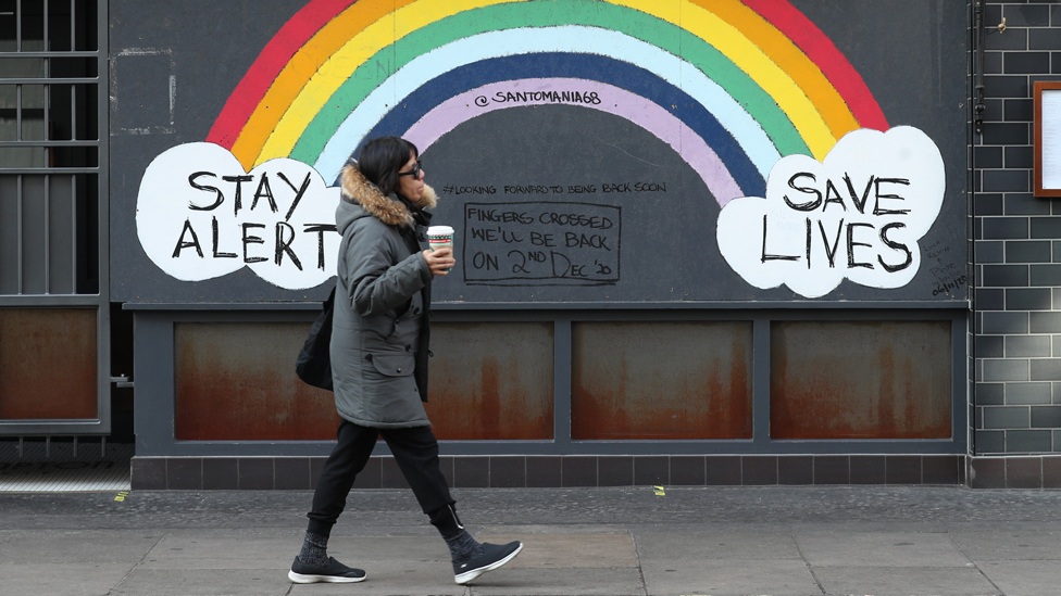 Person walking in front of a rainbow mural