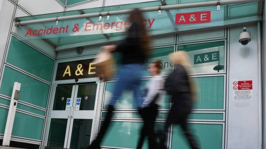 Pedestrians walk past an accident and emergency department