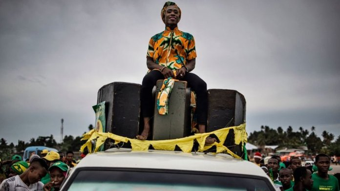 A person sits on a truck as supporters of the ruling Chama Cha Mapinduzi (Revolutionary Party) celebrate the victory of their candidate in the Zanzibar Presidential election on the outskirts of Stone Town, on October 30, 2020.