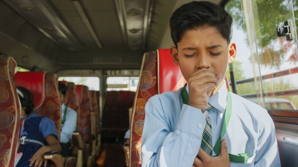Child coughing on a bus.