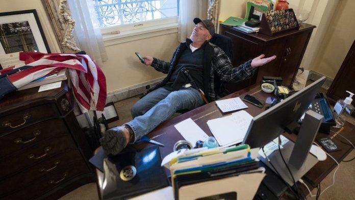 अमेरिकी राष्ट्रपति डोनाल्ड ट्रम्प के एक समर्थक अमेरिकी हाउस के अध्यक्ष नैन्सी पेलोसी के डेस्क पर बैठे हैं