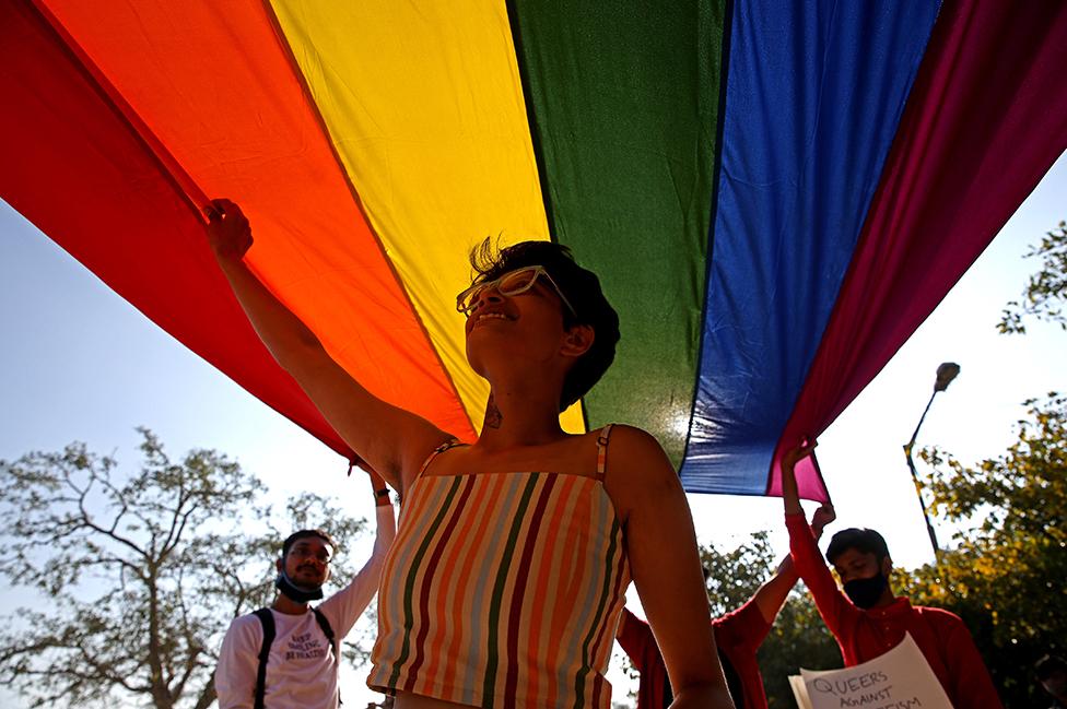 Tres personas participan de una marcha del orgullo gay