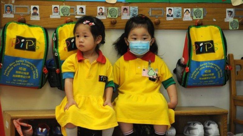 Dos niñas en Hong Kong durante a pandemia de H1N1.