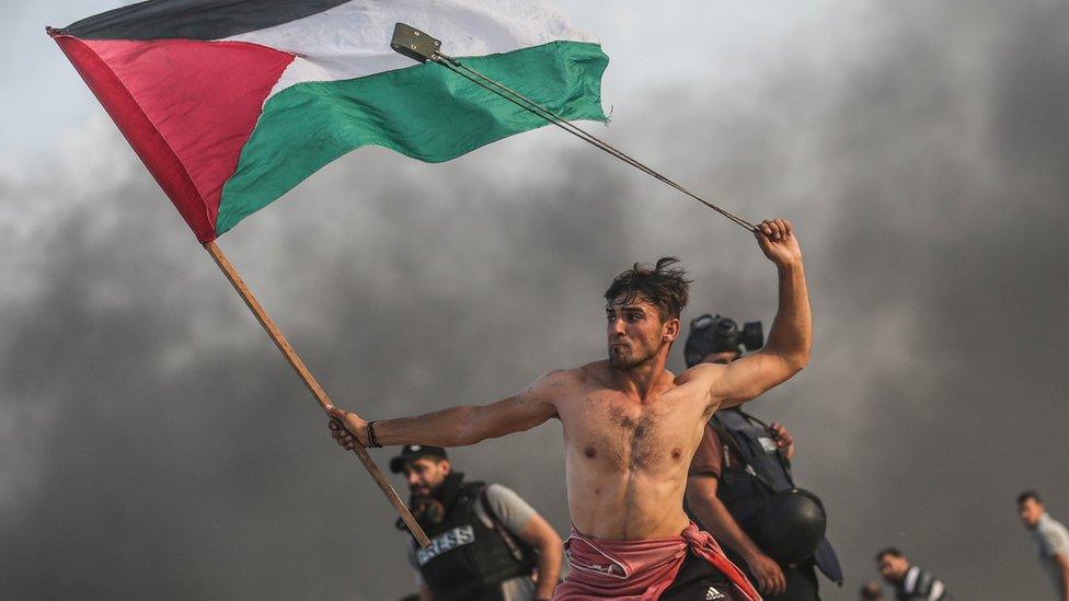 Palestinos lanzan piedras y queman neumáticos en respuesta a las fuerzas israelíes durante una manifestación marítima en la ciudad de Gaza el 22 de octubre de 2018.