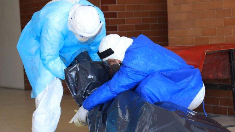 Dos personas mueven el cuerpo de una persona fallecida dentro de una bolsa.