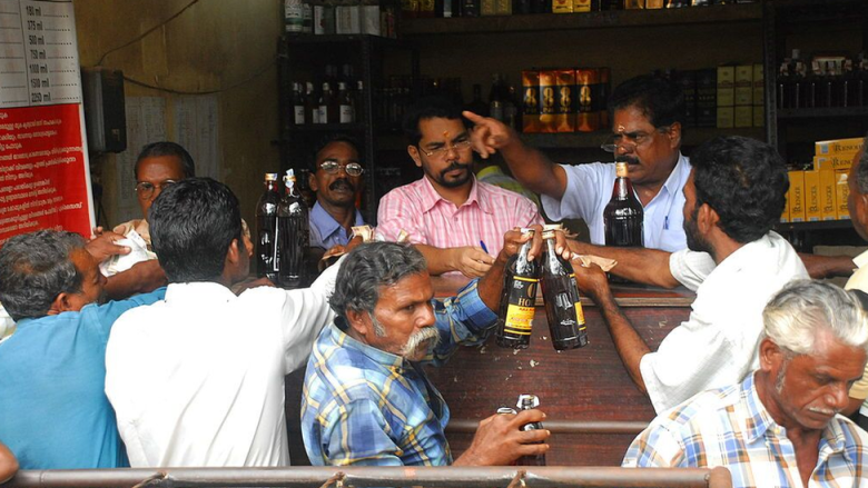 Customers buying liquor from a shop in Kerala, India