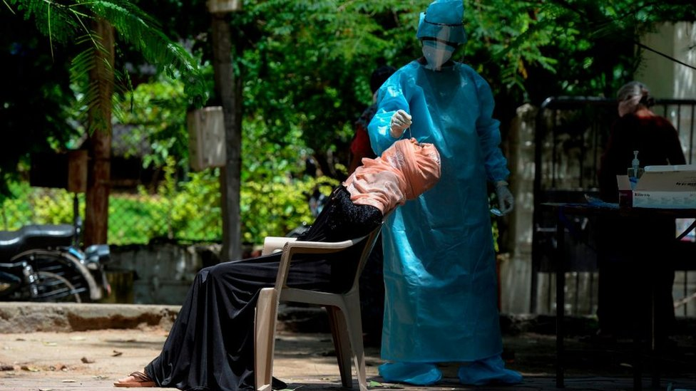 A health worker wearing Personal Protective Equipment (PPE) collects a swab sample from a woman for a free Covid-19 coronavirus test at a Municipal Corporation park in Hyderabad on August 31, 2020.