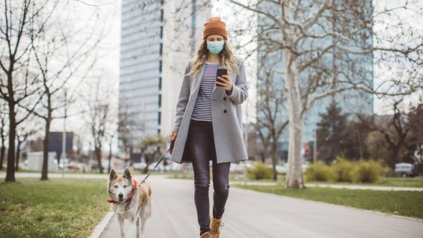 Mujer con mascarilla caminando con un perro.