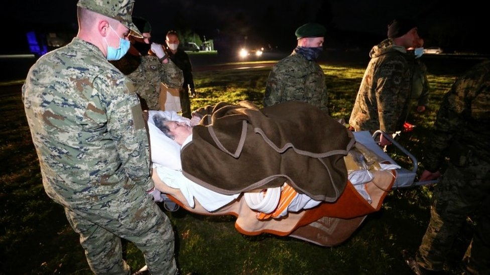 Military personnel carry an ill person on a stretcher to be evacuated to Zagreb by helicopter