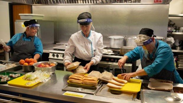 Kitchen staff prepare school lunches for pupils